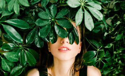 Verzorging bij een vette huid. Gezicht tussen de groene bladeren.