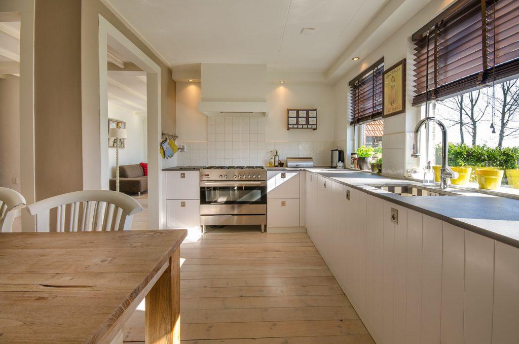 Een grote witte landelijke keuken met veel lichtinval