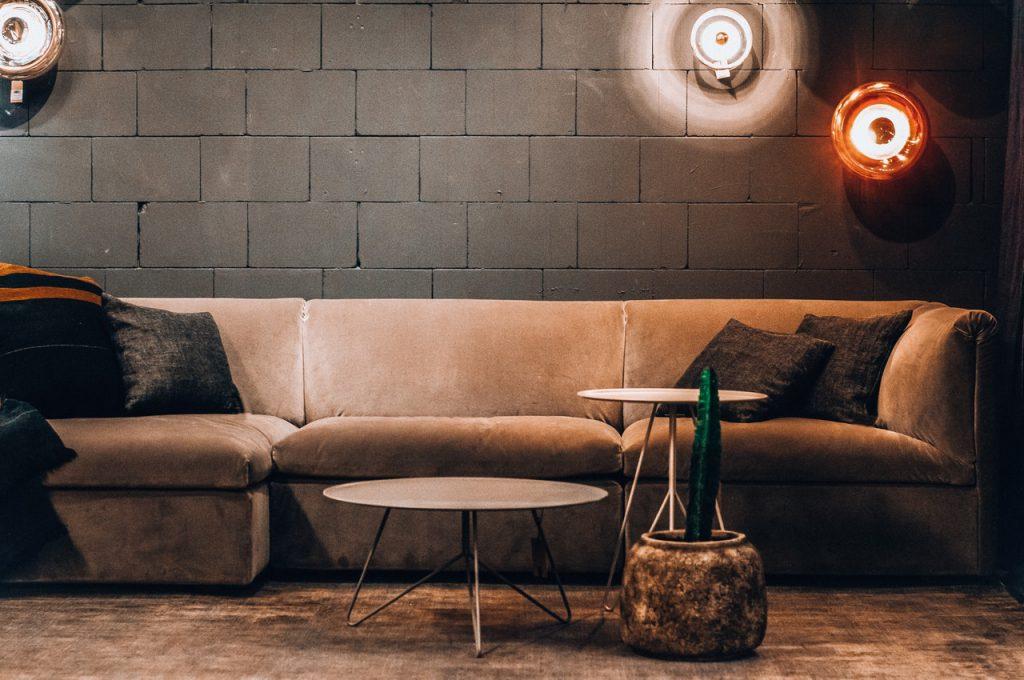 Industrieel wonen met een stoere en mannelijke inrichting. Donkere kleuren en een betonnen muur.
