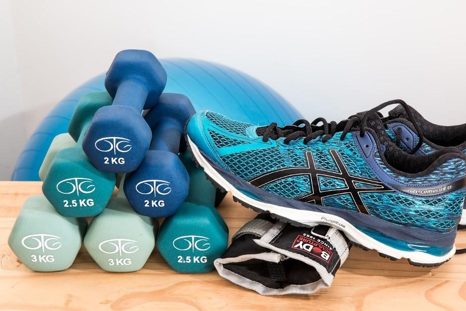 Lichte gewicht dumbbells, hardloopschoenen en een yogabal.